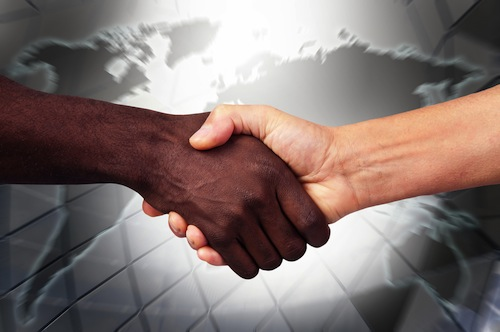 Handshake with black hand and white hand - shutterstock